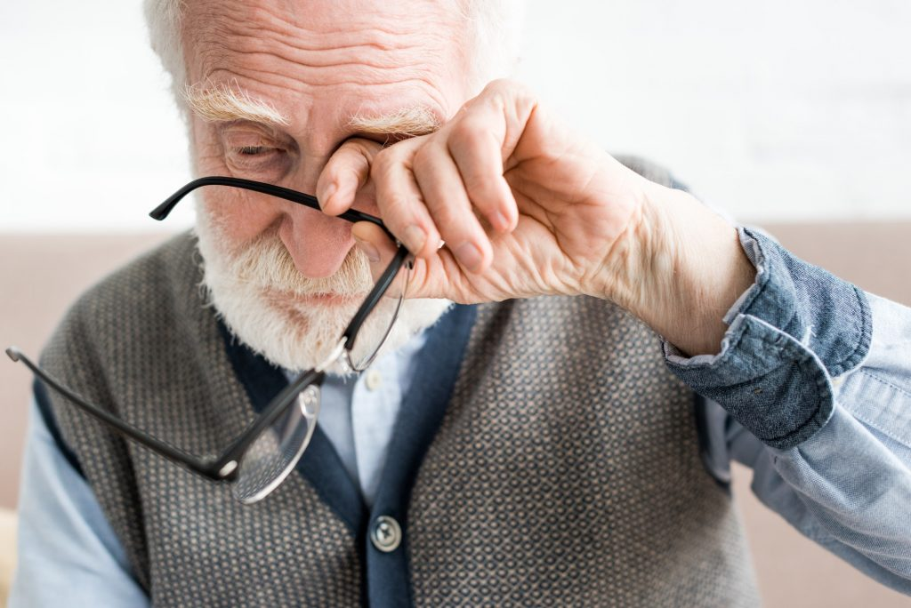Sad senior man holding glasses, and covering eye of his hand